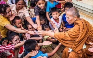 Asian monk giving to children